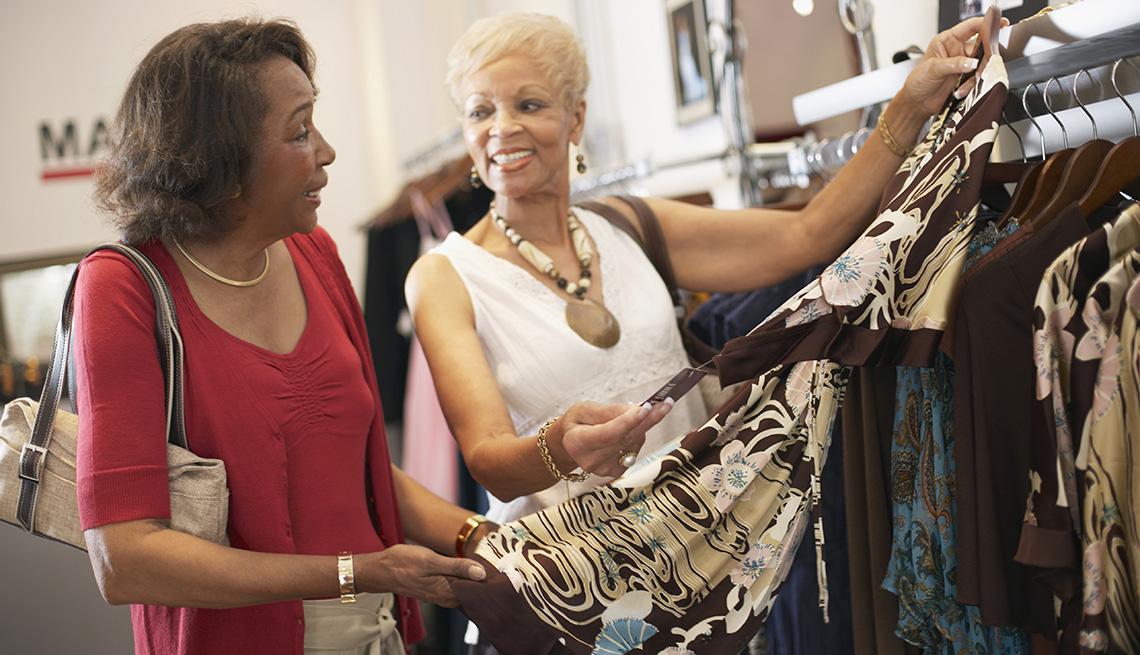 Dos mujeres mirando un vestido en una tienda.