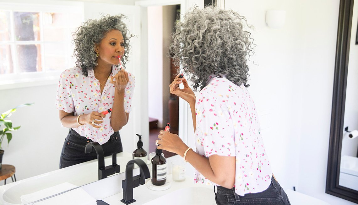A woman applying makeup in front of a mirror in her bathroom