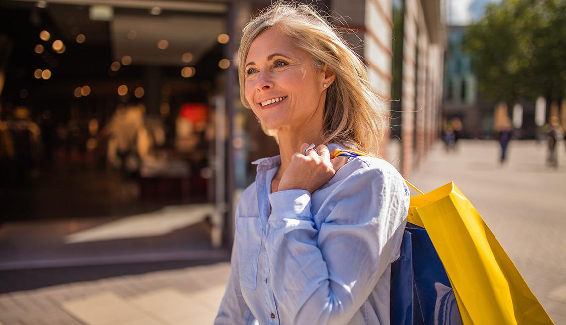 Una mujer caminando por una calle mientras llevaba bolsas de compras sobre su hombro.