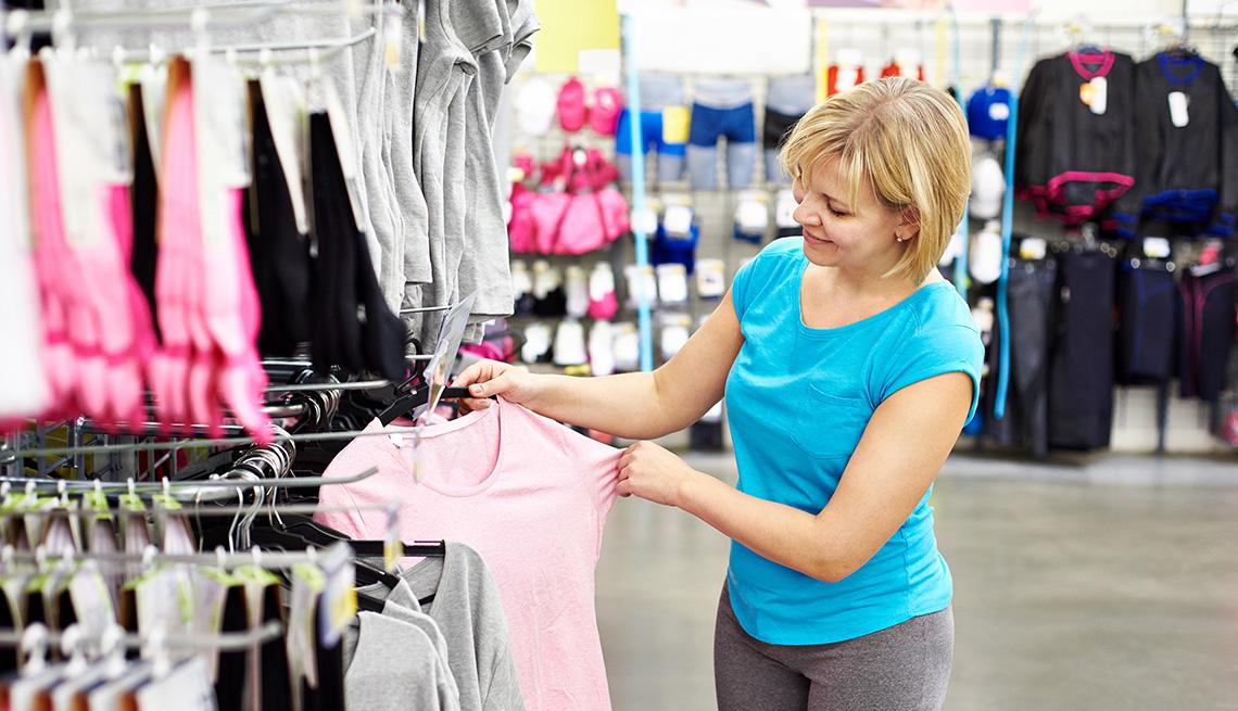 Una mujer mirando una camiseta rosa en una tienda de ropa deportiva.