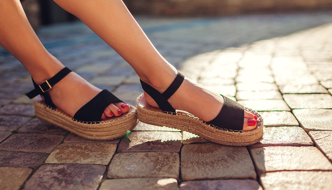 A closeup of a woman's feet wearing a pair of black sandals outdoors