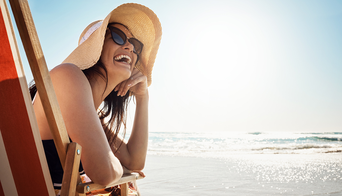A woman is laughing at the beach