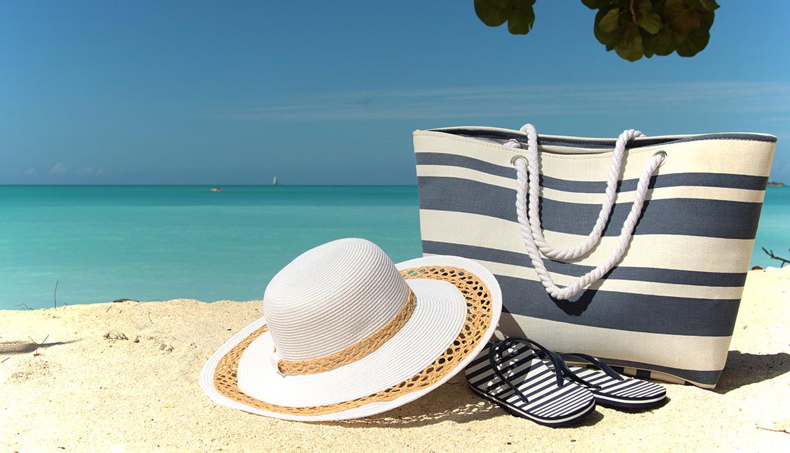 Sombrero, bolso de playa y chanclas a la orilla del mar.