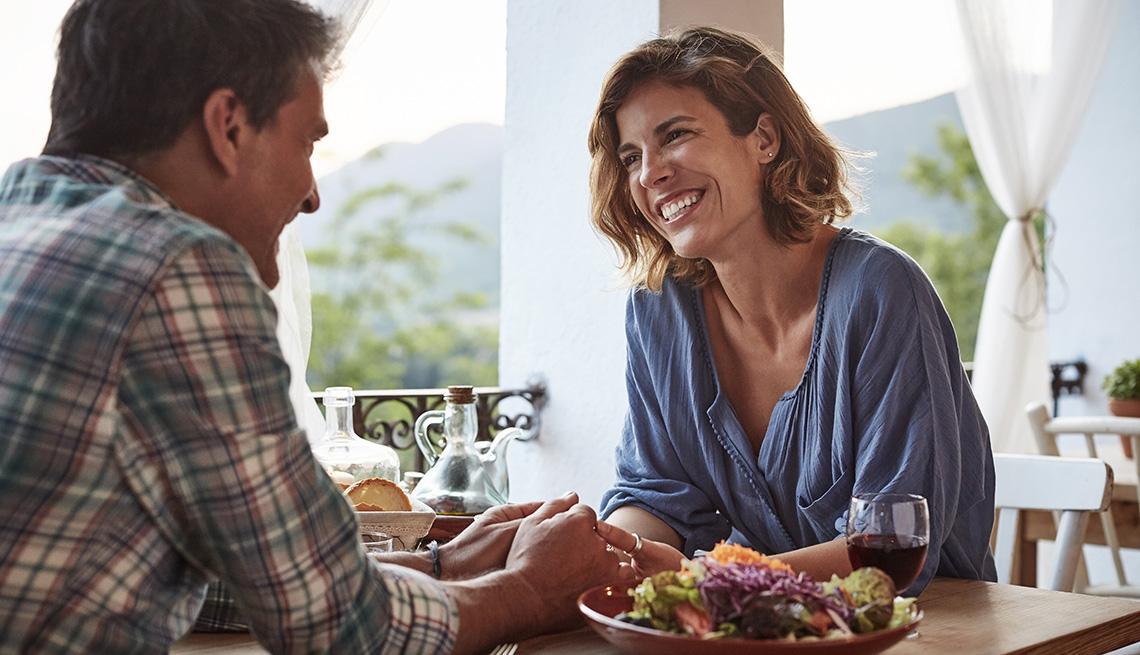 Una pareja de hombre y mujer luciendo feliz mientras se toman de la mano sentados en un restaurante.