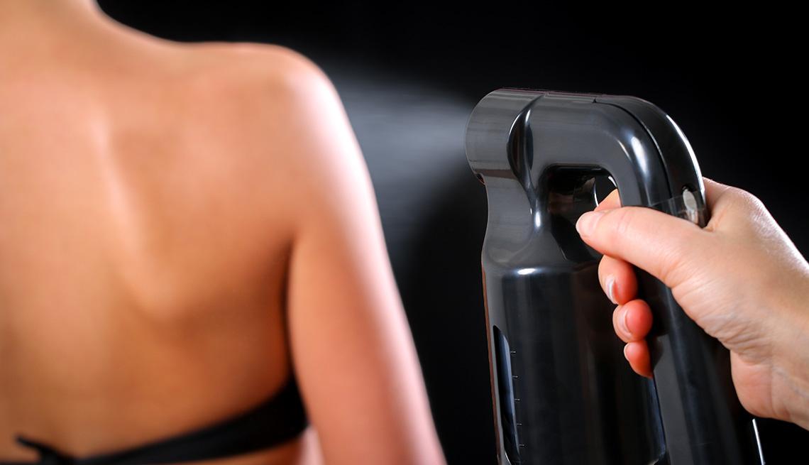 item 3 of Gallery image - Una mujer obteniendo un bronceado profesional en rociador.