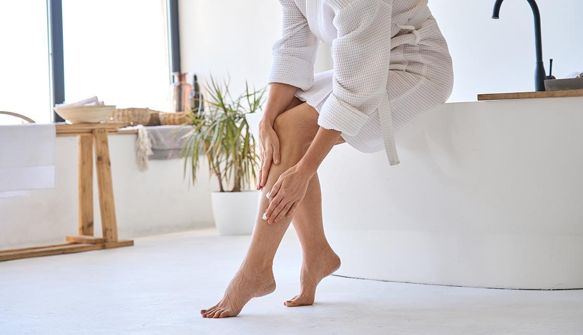 item 11 of Gallery image - Mujer aplicando crema en las piernas.