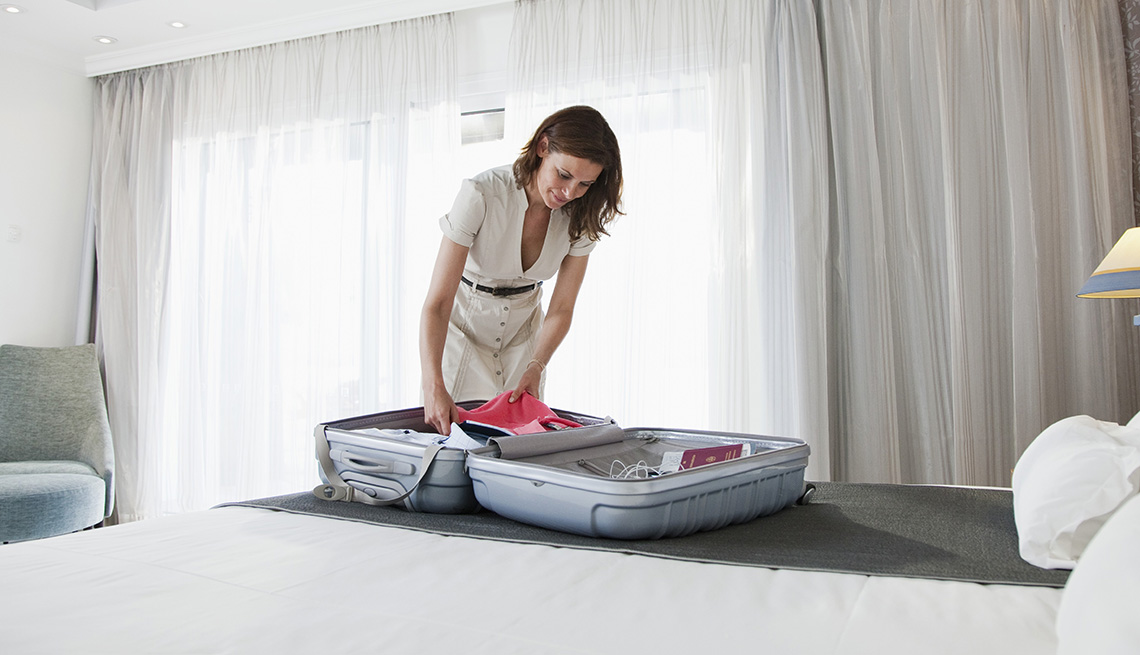 item 10 of Gallery image - A woman packing suitcase in her hotel room