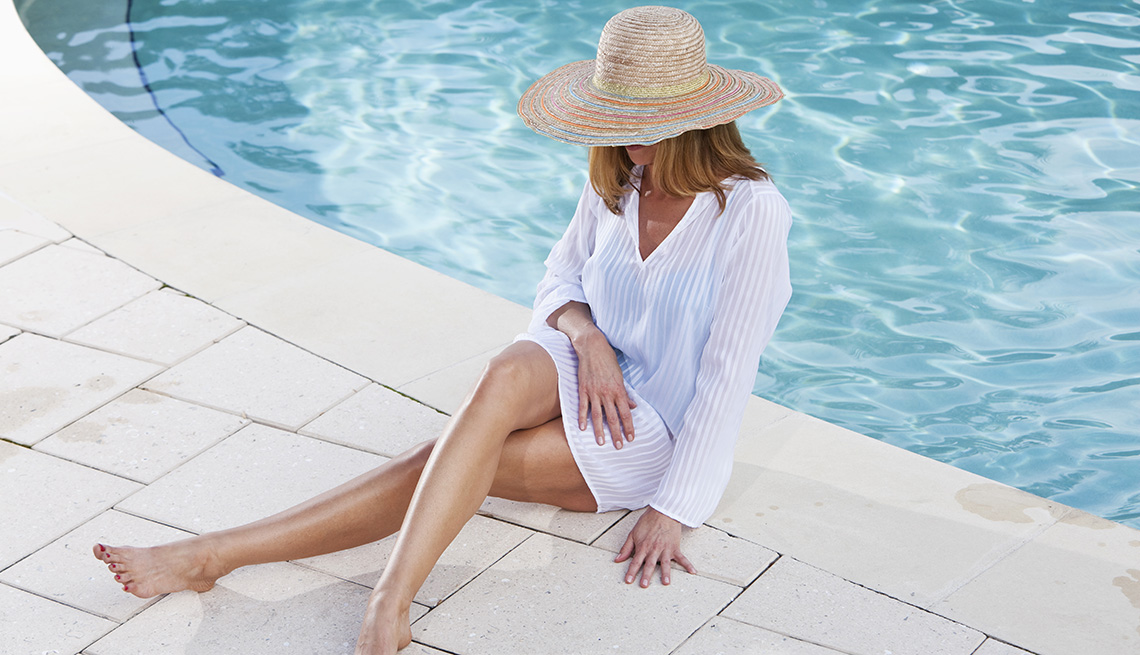 Una mujer sentada al borde de una piscina con un trajer corto luciendo sus piernas.