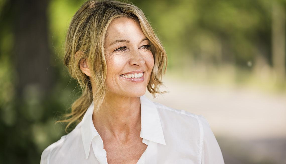 Una mujer sonriendo afuera en un día soleado.