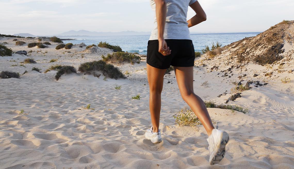 Una mujer en pantalones cortos caminando en la playa.