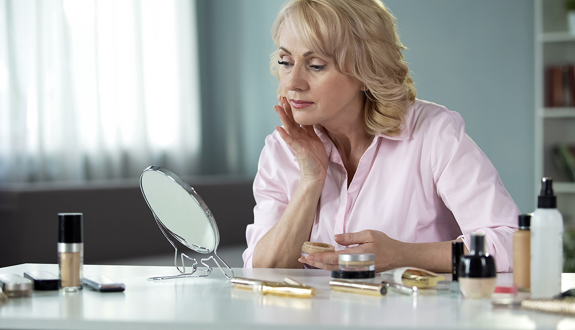 Woman applying makeup in front of a small mirror on a desk