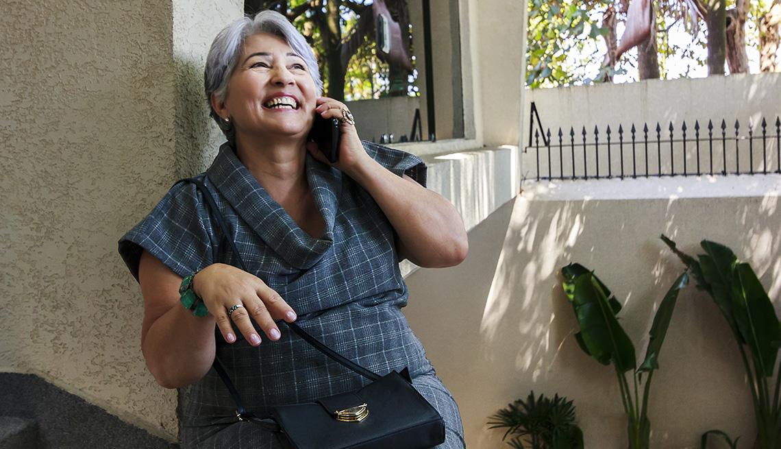 Una mujer está sonriendo mientras habla por un teléfono celular afuera.