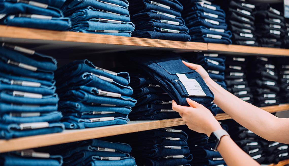 Una mujer sosteniendo un par de jeans en una tienda de ropa.
