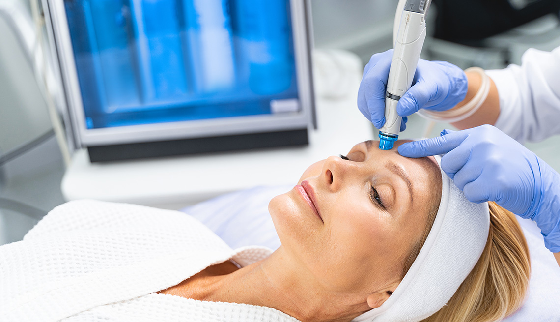 item 8 of Gallery image - A woman lying down undergoing microdermabrasion treatment