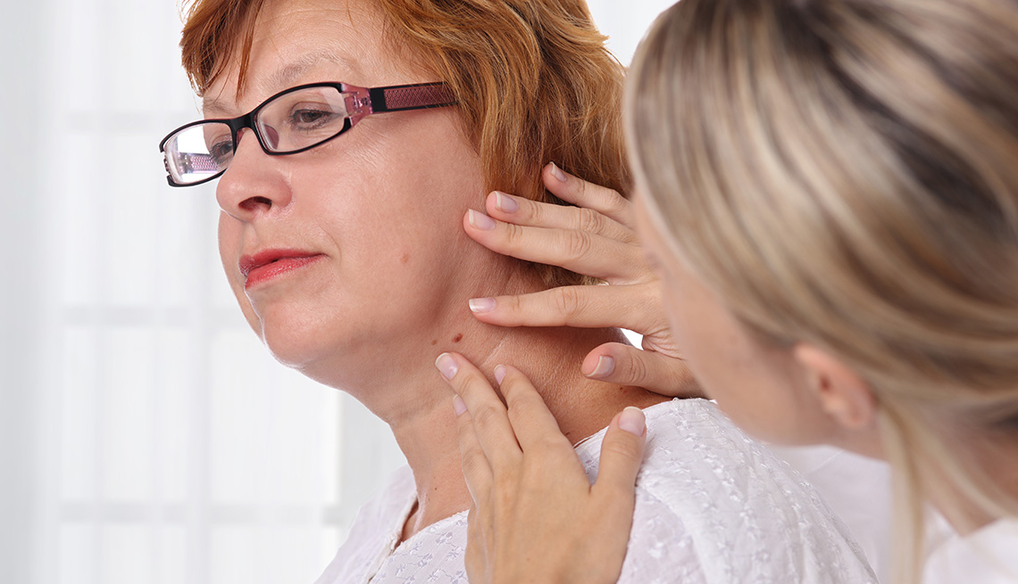 A dermatologist checking a dark spot in the area of a female patient's face and neck area