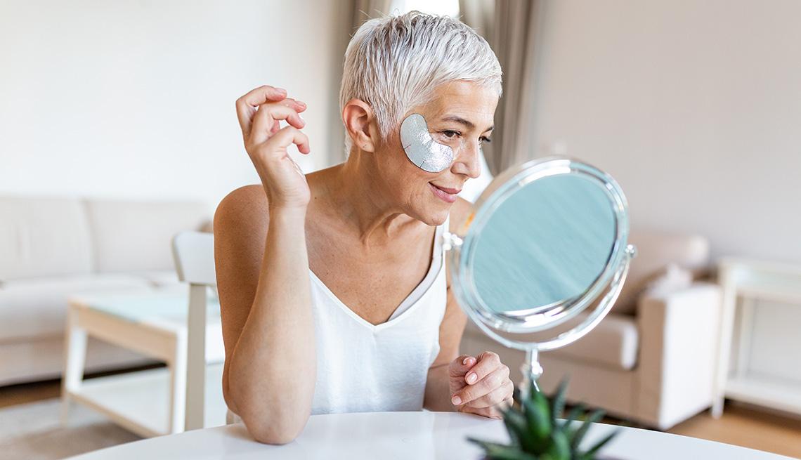 Una mujer sonriendo, se aplica parches debajo de los ojos mientras se mira en el espejo.