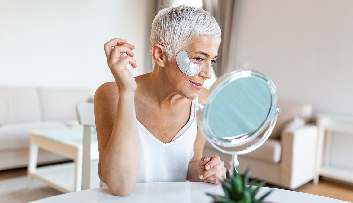 A woman wearing an eye mask looks into a vanity mirror