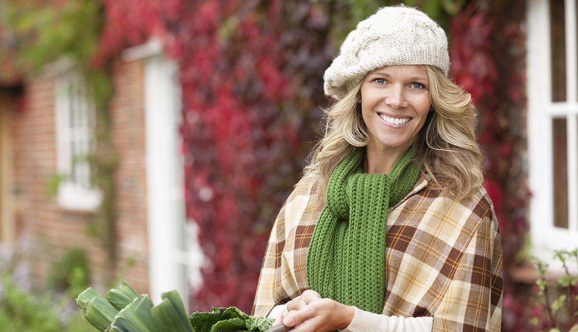 Una mujer vistiendo ropa de otoño sosteniendo una canasta al aire libre.