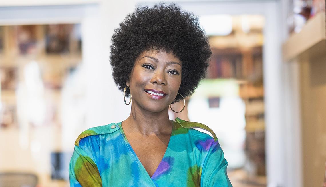 Una mujer con cabello rizado natural sonriendo.