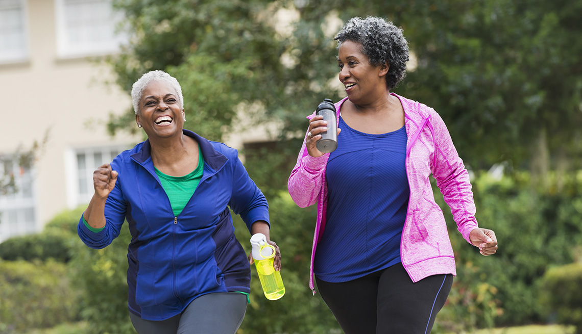 item 9 of Gallery image - Two women taking a walk together while holding water bottles