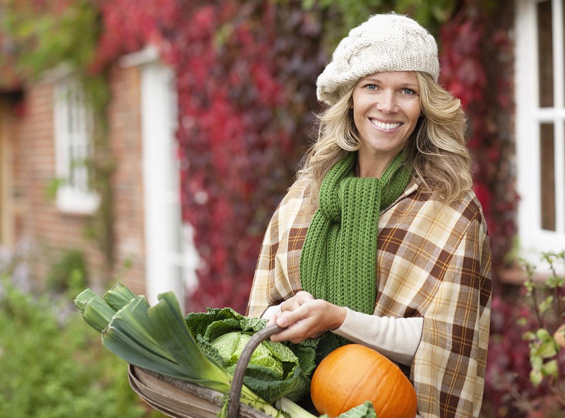 Una mujer vestida para el otoño sosteniendo una canasta de verduras y una calabaza.