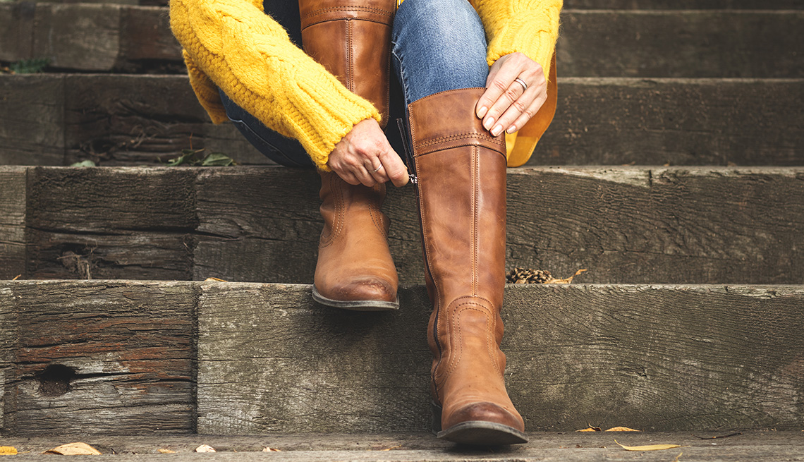 A woman sitting on the stairs and fastening the zipper on her brown leather boots