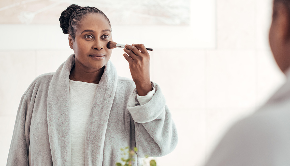 A woman applies foundation on her face with a brush