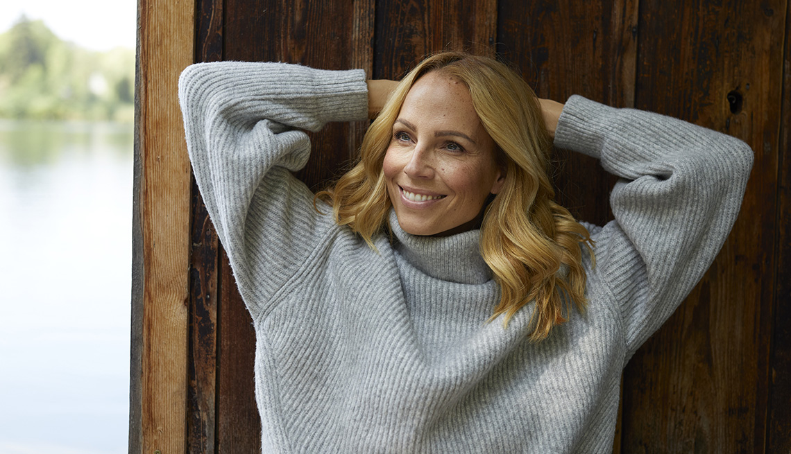 A woman wearing a sweater smiling outside