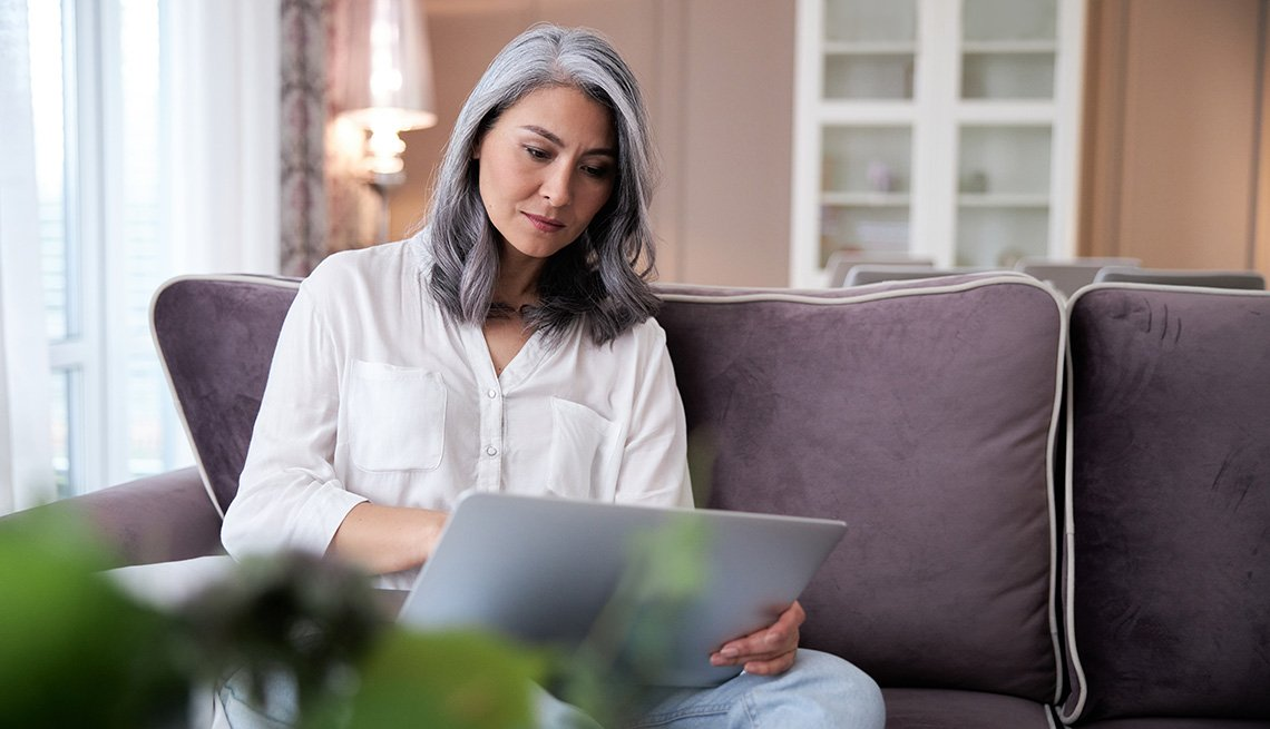 A woman sitting on a sofa using a laptop