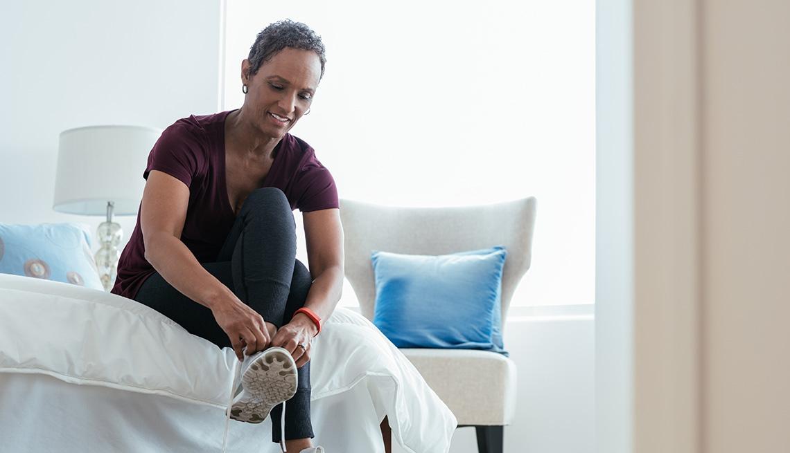 Una mujer poniéndose y ajustando zapatillas en su dormitorio.