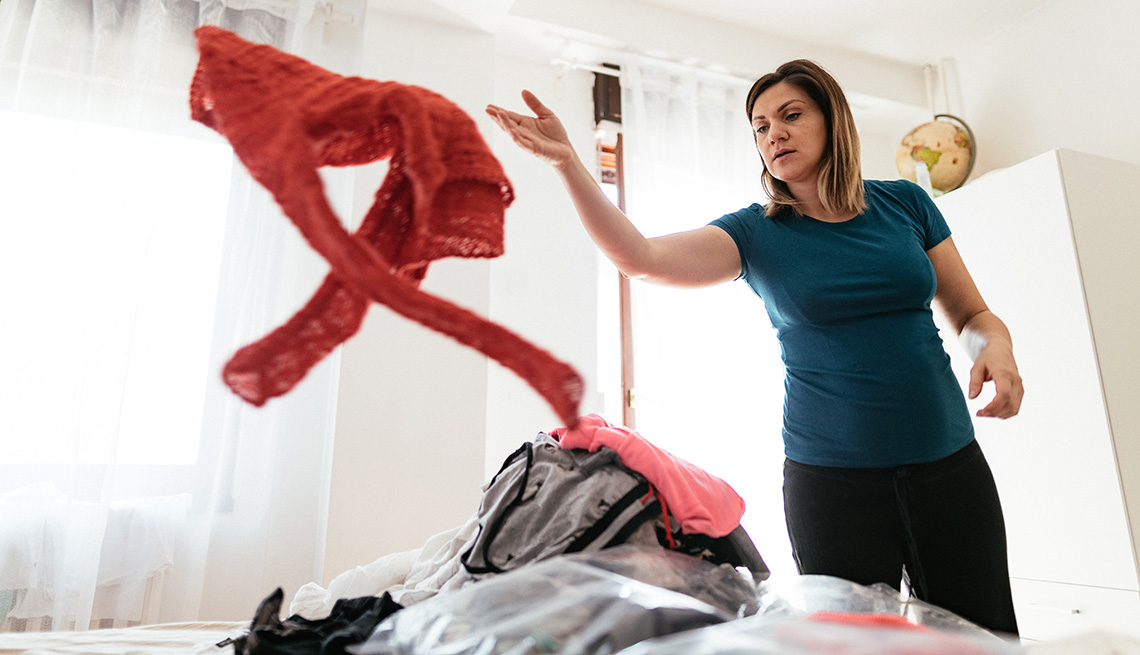 A woman tosses a piece of clothing while sorting through clothes in bedroom