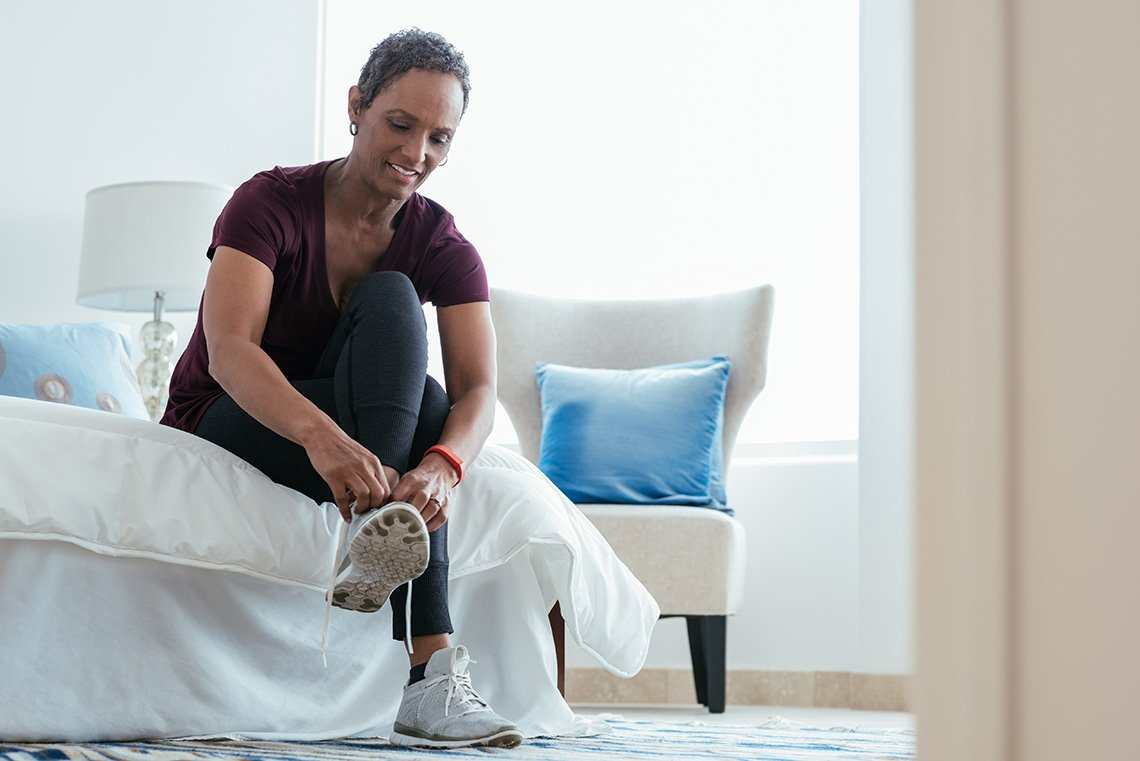 A woman putting on sneakers in bedroom