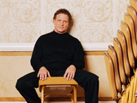 Albert Brooks with stacks of chairs.