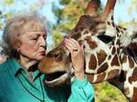 Betty White author of Betty and Friends - My Life at the Zoo kisses a giraffe