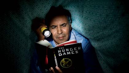 Mature man reading The Hunger Games in bed