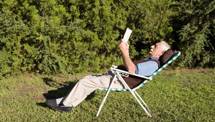 Classic literature and popular novels for seniors- Great Gatsby book cover- mature man reading book outdoors