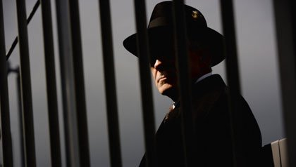 Tough guy detective looking through steel bars