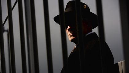Tough guy detective looking through steel bars