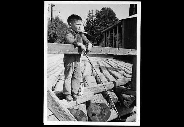 Neil Young at almost five, fishing on a bridge over the Pigeon River, Omemee, Ontario in August 1950
