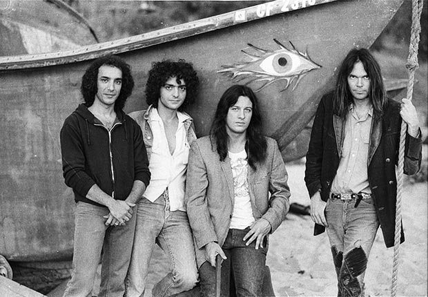 """Rock band Crazy Horse. From left to right, Ralph Molina, Billy Talbot, Frank """"Poncho"""" Sampedro and Neil Young on Malibu Beach in 1975"""