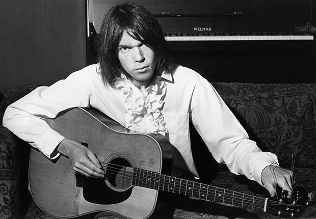 Neil Young playing guitar as he poses for a portrait at a a Warner Brothers rented house in Chelsea, West London
