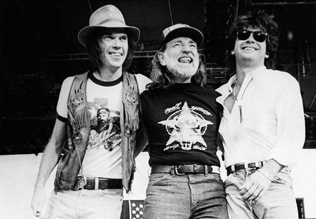 Singer-songwriters Neil Young, Willie Nelson, and John Mellencamp stand together on stage during the 1985 Farm Aid Concert
