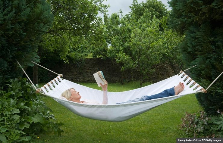 Woman reading book in hammock, Summer Book Recommendations (Henry Arden/Cultura RF/Getty Images)
