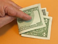 Hand holding money. What happens when we pay others to live our lives? (Norberto Lauria/Alamy)