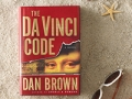 Beach scene with classic book THE DA VINCI CODE perched up in th