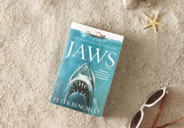 Beach scene with classic book JAWS perched up in the sand, Power of 50 Summer Books