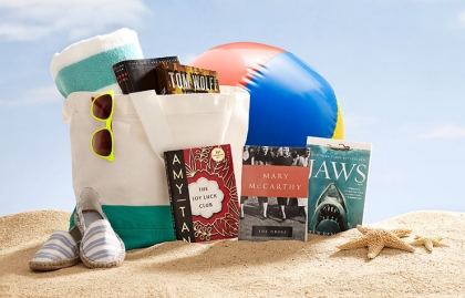 Beach scene with classic books perched up in the sand, Power of 50 Summer Books