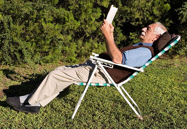 A man reads a book outside, 21 Great Novels It's Worth Finding Time to Read