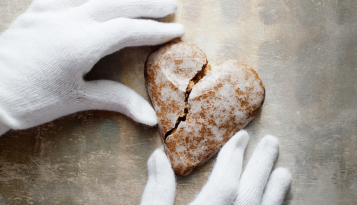 Two white-gloved hands holding together a broken heart-shaped cookie