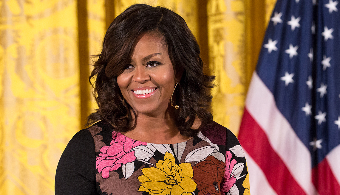 michelle obama smiling in front of yellow curtain and american flag